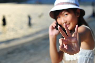 Little Chinese Asian girl on beach with phone