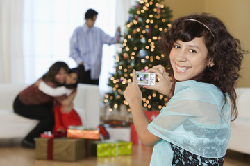 Hispanic girl photographing family opening Christmas gifts