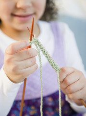 Hispanic girl knitting with yarn