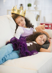 Hispanic sisters in costumes sleeping on couch