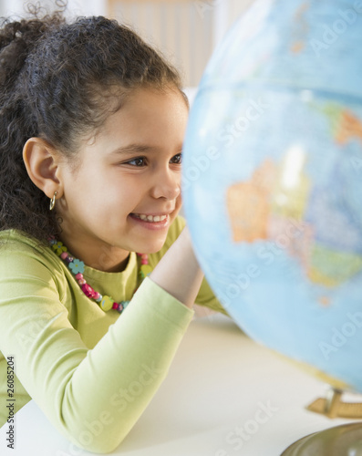 Hispanic girl looking at globe