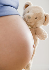 Pregnant Hispanic woman holding teddy bear