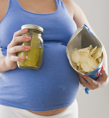 Pregnant Hispanic woman holding pickles and potato chips