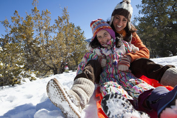 Mother and daughter sledding in snow