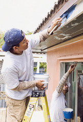 Latin man painting roof eaves