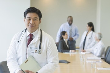 Chinese doctor in conference room with co-workers