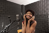Mixed race woman singing in recording studio
