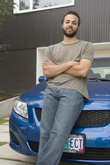 Mixed race man leaning on car hood