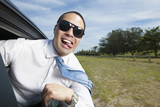 Asian businessman riding in car with head out window