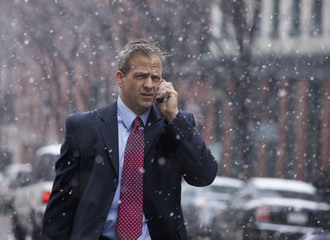 Caucasian businessman walking in snow and talking on cell phone