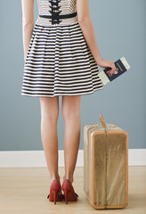 Mixed race woman with passport and suitcase