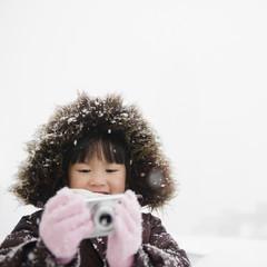 Chinese girl in snow using digital camera