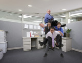 Businessman holding co-workers on his back in office