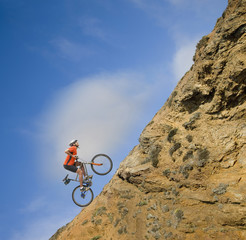 African man riding bicycle up steep hill