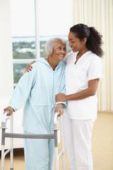African American nurse helping senior woman with walker