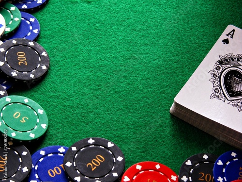 Poker chips & cards on green felt background
