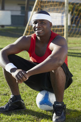 Black man sitting on soccer ball