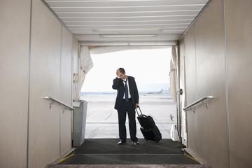 Hispanic businessman standing on jetway