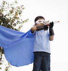 Korean boy in superhero costume aiming gun