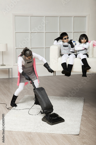 Asian superhero mother lifting sofa to vacuum underneath