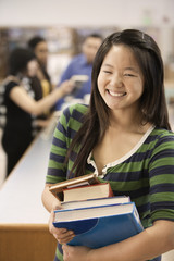 Asian student holding books in school library