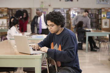 Student with laptop in school library