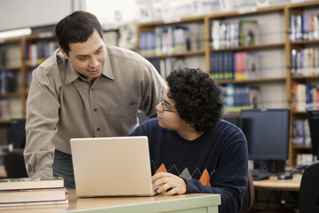 Librarian helping student with laptop in school library