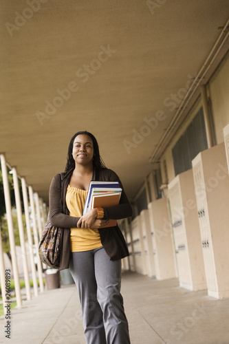 Student carrying books in school corridor