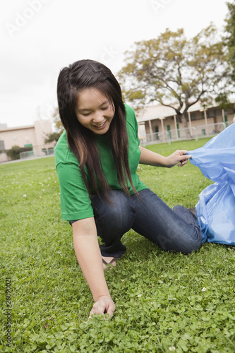 Asian student picking litter on school grounds
