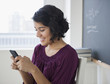 Hispanic woman text messaging on cell phone