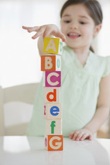 Mixed race girl stacking alphabet blocks