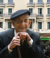 Senior Hispanic man in suit and cap
