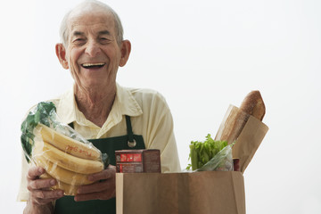 Senior Hispanic grocer loading paper bag with food