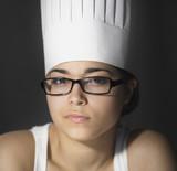 Hispanic woman in chefÕs hat and eyeglasses