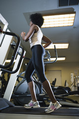 Mixed race woman running on treadmill in gym