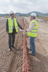 Hispanic businessman and construction worker standing in field