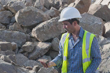 Hispanic construction worker looking at rock