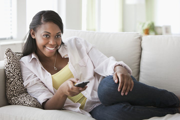 African American woman laying on sofa using remote control
