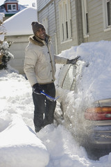 Mixed race man removing snow from car