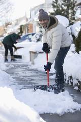 Mixed race man shoveling snow from sidewalk