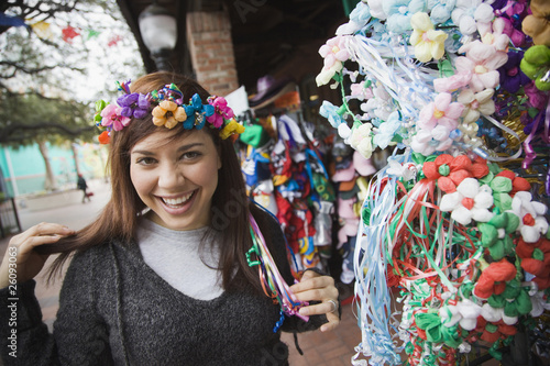 Mixed race woman trying on headdress at souvenir shop