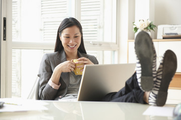 Chinese businesswoman working at desk with feet up