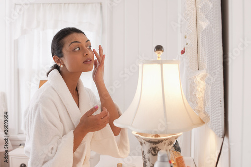 Middle Eastern woman applying lotion