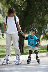 mother and son rollerskating in park