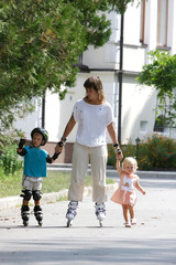 mother with two children rollerskaing in park