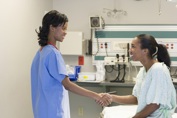 Black doctor greeting patient in hospital