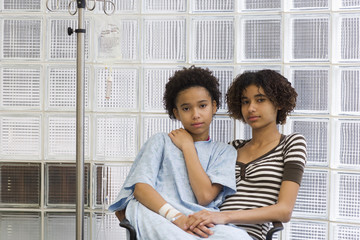 Girl sitting with sister receiving IV