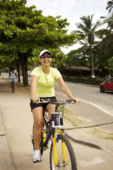 Mixed race woman riding bicycle on sidewalk