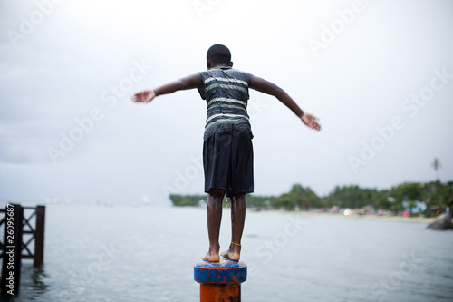 Boy on pipe about to jump in the water