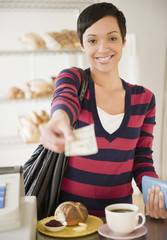 Mixed race woman paying for food in bakery